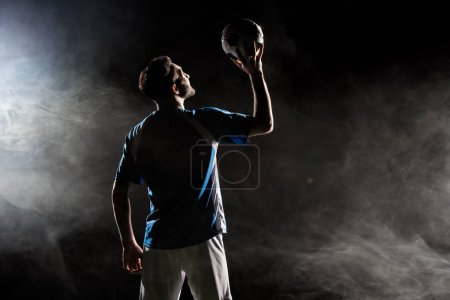 Photo for Silhouette of player in uniform holding ball above head on black with smoke - Royalty Free Image
