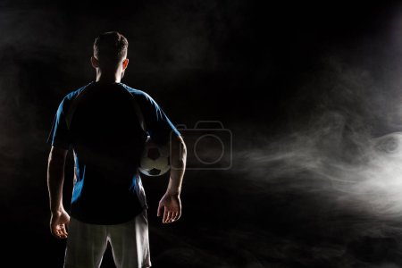 Photo for Silhouette of man standing in uniform with ball on black with smoke - Royalty Free Image