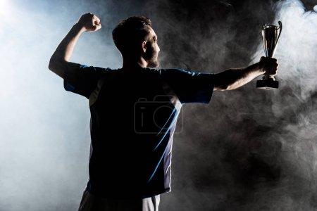 Photo pour Silhouette de champion tenant trophée sur noir avec fumée - image libre de droit