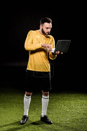 Photo for Bearded coach looking at laptop and blowing whistle isolated on black - Royalty Free Image