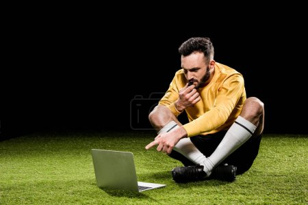 Photo for Handsome referee blowing in whistle and pointing with finger at laptop while sitting on grass isolated on black - Royalty Free Image
