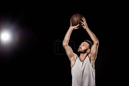 handsome basketball player throwing ball on black background