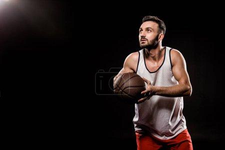 Photo pour Joueur de basket sérieux tenant ballon sur fond noir - image libre de droit