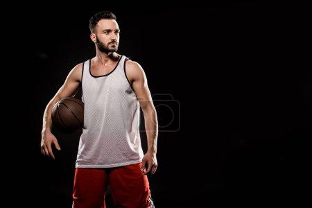 Photo pour Confiant de basketteur tenant boule isolée sur fond noir - image libre de droit