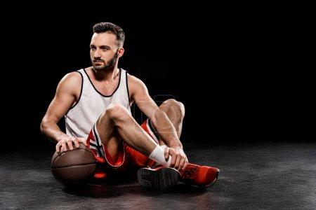 Photo pour Graves de basketteur assis avec ballon sur fond noir - image libre de droit