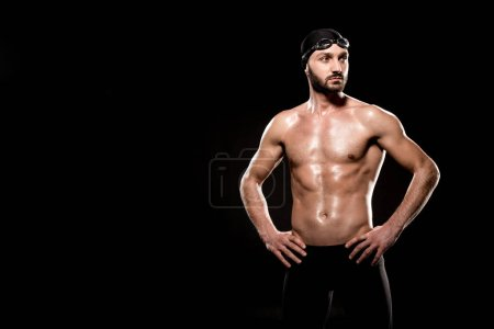 Photo for Muscular swimmer standing in swimming cap and swim goggles isolated on black - Royalty Free Image