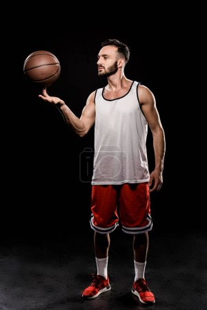 Photo for Handsome basketball player spinning ball on finger on black background - Royalty Free Image