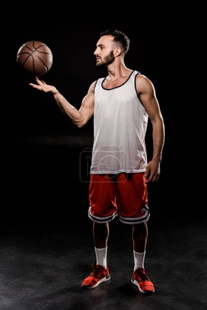 Photo for Bearded basketball player spinning ball on finger on black background - Royalty Free Image