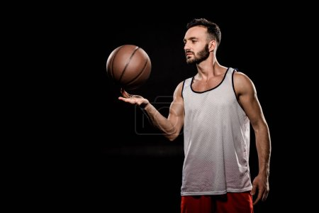 Photo for Handsome basketball player spinning ball on finger isolated on black - Royalty Free Image