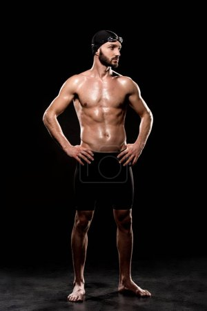 Photo for Handsome swimmer standing in swimming cap and swim goggles on black background - Royalty Free Image
