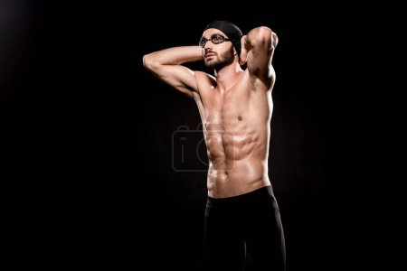Photo for Confident swimmer standing in swimming cap and posing isolated on black - Royalty Free Image