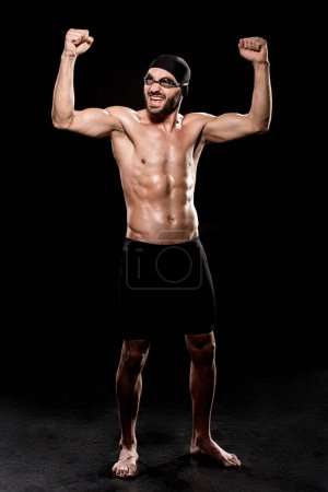 Photo for Cheerful swimmer standing in swimming cap and showing muscles on black background - Royalty Free Image
