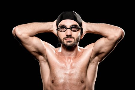 Photo for Handsome swimmer posing in swimming cap and goggles isolated on black - Royalty Free Image