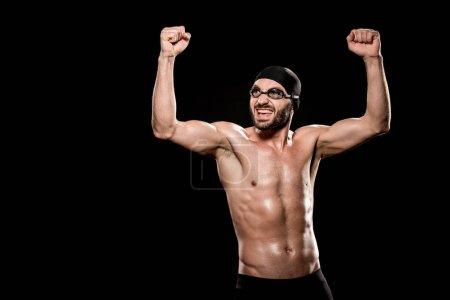 Photo pour Nageur gai permanent en natation cap et célébrant la victoire isolée sur fond noir - image libre de droit