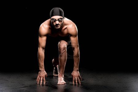 Photo for Handsome swimmer standing in start position on black background - Royalty Free Image