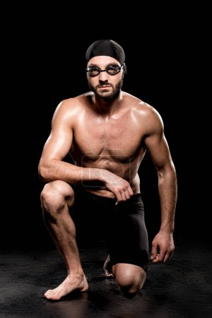 Photo for Athletic swimmer sitting in swimming cap and goggles on black background - Royalty Free Image