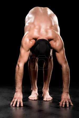 Photo for Muscular man standing in start position on black background - Royalty Free Image