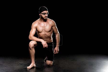 Photo for Athletic sportsman sitting in swimming cap and goggles on black background - Royalty Free Image