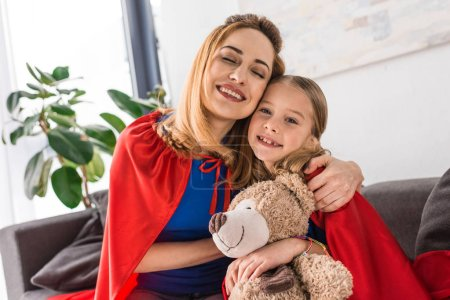 Photo for Hugging and smiling mother and kid in red cloaks holding teddy bear - Royalty Free Image