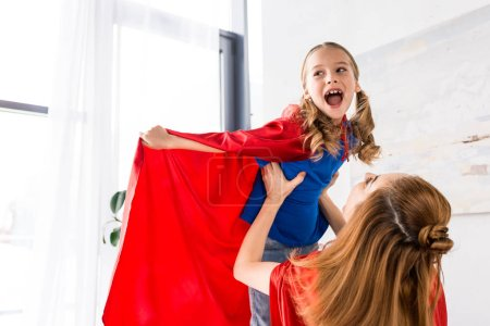 Photo for Happy mother and kid in red cloaks playing at home - Royalty Free Image