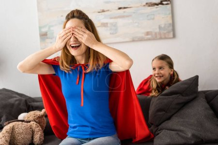 Photo for Smiling mother and cute kid in red cloaks playing hide-and-seek at home - Royalty Free Image