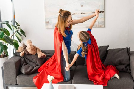 Photo for Smiling daughter and mother playing on sofa at home - Royalty Free Image