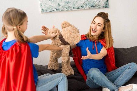 Foto de Hermosa madre e hija Linda en mantos rojos jugando con oso de peluche en casa - Imagen libre de derechos