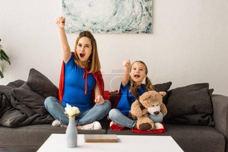Photo pour Mère et fille excitées assis sur le canapé et riant à la maison - image libre de droit