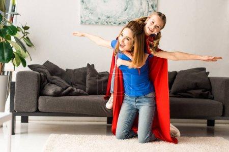 Foto de Lindo niño y madre en capas rojo jugando en casa - Imagen libre de derechos