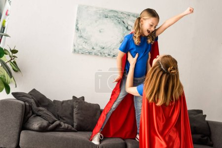 Photo for Kid and mother in red cloaks playing at home - Royalty Free Image