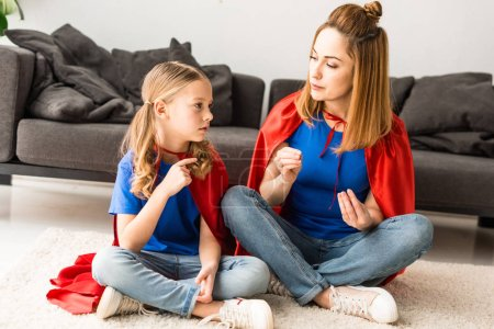 Photo for Daughter and mother sitting on floor and talking at home - Royalty Free Image