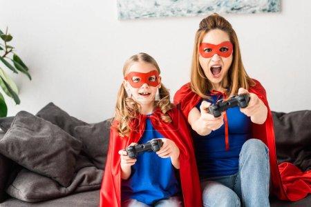 Photo pour Belle mère et la fille en rouges masques et capes jeu vidéo à la maison - image libre de droit