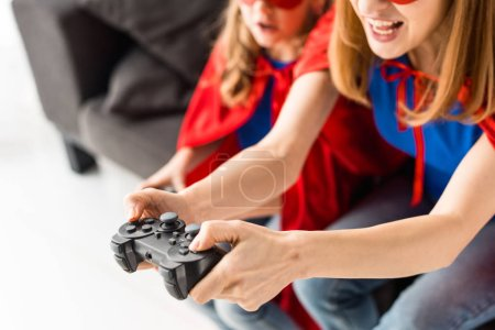 Photo pour Vue partielle de la femme et l'enfant qui joue le jeu vidéo - image libre de droit