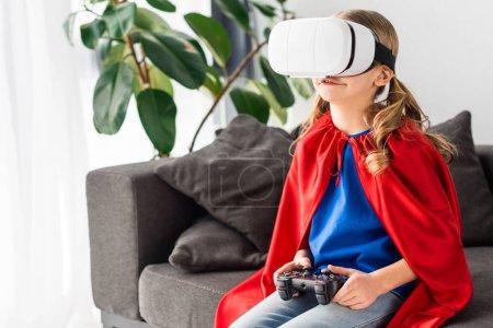 Foto de Niño lindo en capa roja y casco de realidad virtual juego de vídeo - Imagen libre de derechos