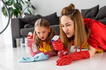 madre e hija en capas rojas y guantes de goma lavando piso en casa