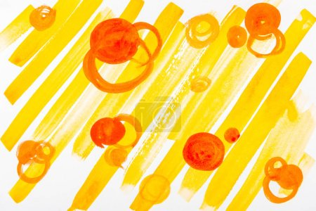 Foto de Vista superior de círculos anaranjados y pinceladas amarillas sobre fondo blanco - Imagen libre de derechos