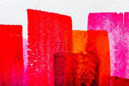 Photo pour Vue de dessus des coups de pinceau aquarelle rose, orange et rouge sur papier blanc - image libre de droit
