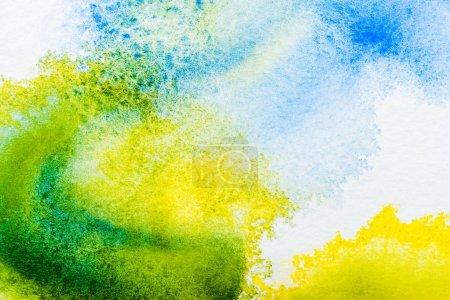 Foto de Vista superior de azul, amarillo y verde acuarela derrames sobre papel blanco - Imagen libre de derechos