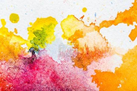 Photo pour Vue de dessus de jaune, orange et rose aquarelle déversements sur papier blanc - image libre de droit