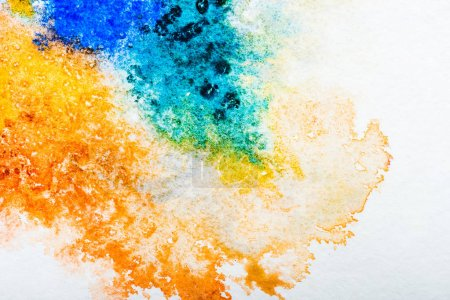 Photo for Top view of blue and orange watercolor spills on white paper - Royalty Free Image