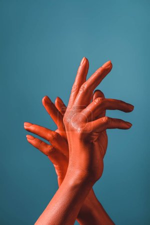 Photo for Partial view of woman gesturing with coral colored hands on blue background,  color of 2019 concept - Royalty Free Image