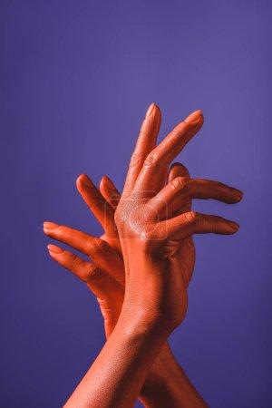 vista parcial de la mujer con las manos de color coral sobre fondo violeta, color de 2019 concepto