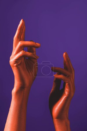 Photo for Partial view of woman gesturing with coral colored hands on violet background, color of 2019 concept - Royalty Free Image