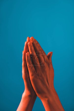 Photo for Partial view of  woman showing pray sign by coral colored hands on blue background, color of 2019 concept - Royalty Free Image