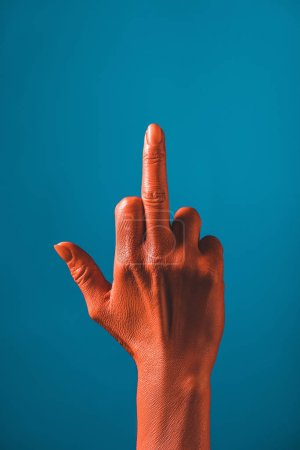 Photo for Cropped view of woman showing middle finger on coral colored hand on blue background,  color of 2019 concept - Royalty Free Image