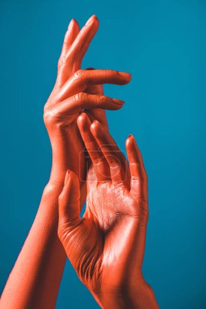 Photo for Cropped view of coral colored female hands on blue background, color of 2019 concept - Royalty Free Image