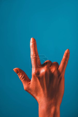 Photo for Cropped view of woman showing rock sign by coral colored hand on blue background, color of 2019 concept - Royalty Free Image