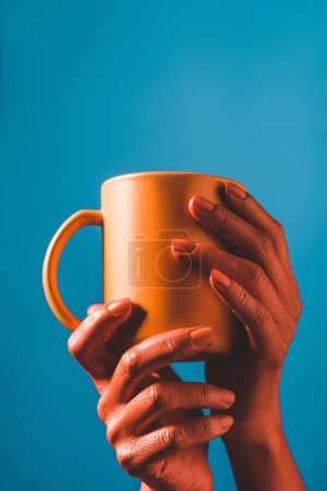 Photo for Cropped view of coral colored female hands with coral coffee cup on blue background, color of 2019 concept - Royalty Free Image