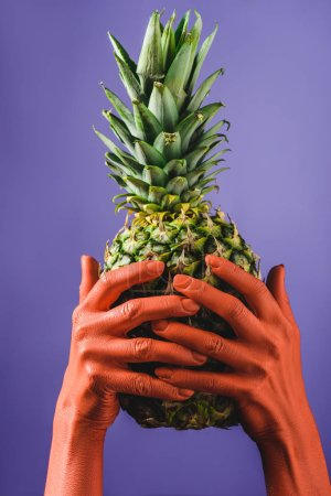 Photo for Cropped view of woman holding ripe pineapple fruit in coral colored hands on violet background, color of 2019 concept - Royalty Free Image