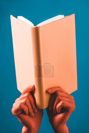 Photo for Cropped view of woman with coral colored hands holding coral book on blue background, color of 2019 concept - Royalty Free Image